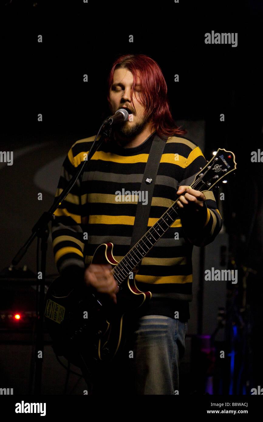 man playing guitar in rock band - Stock Image