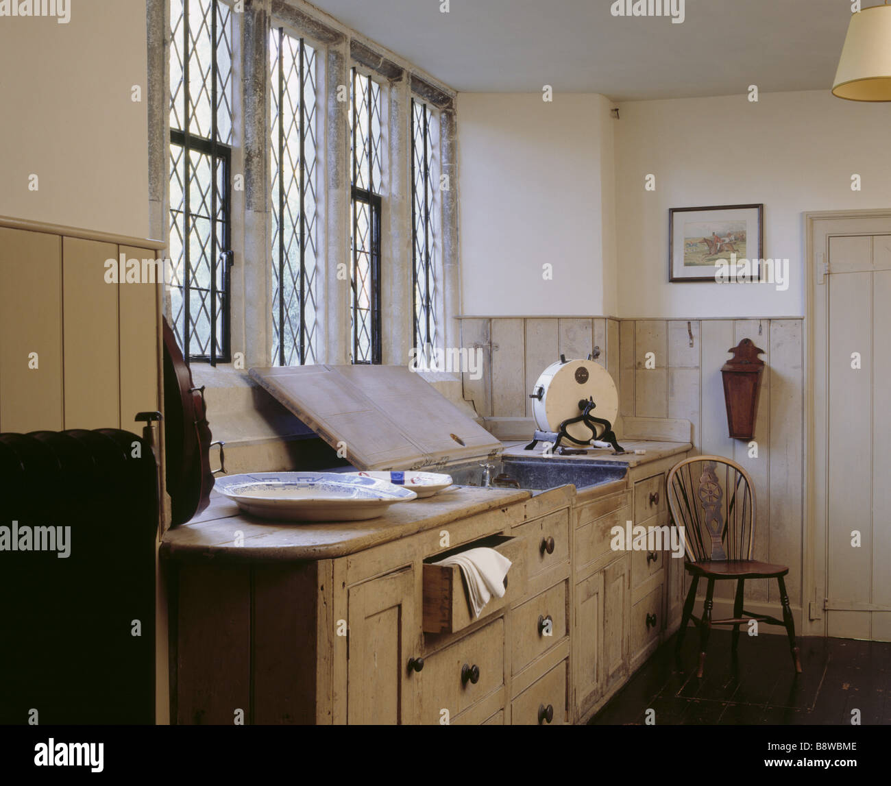 Room view of the Butler s Pantry at Ightham Mote showing the windows sink part of radiator and the wooden kitchen Stock Photo