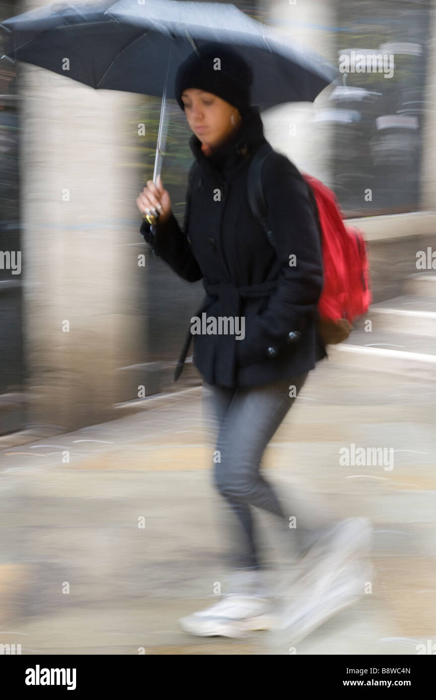 Woman walking in the rain under black umbrella with red rucksack Venice Italy Europe March - Stock Image