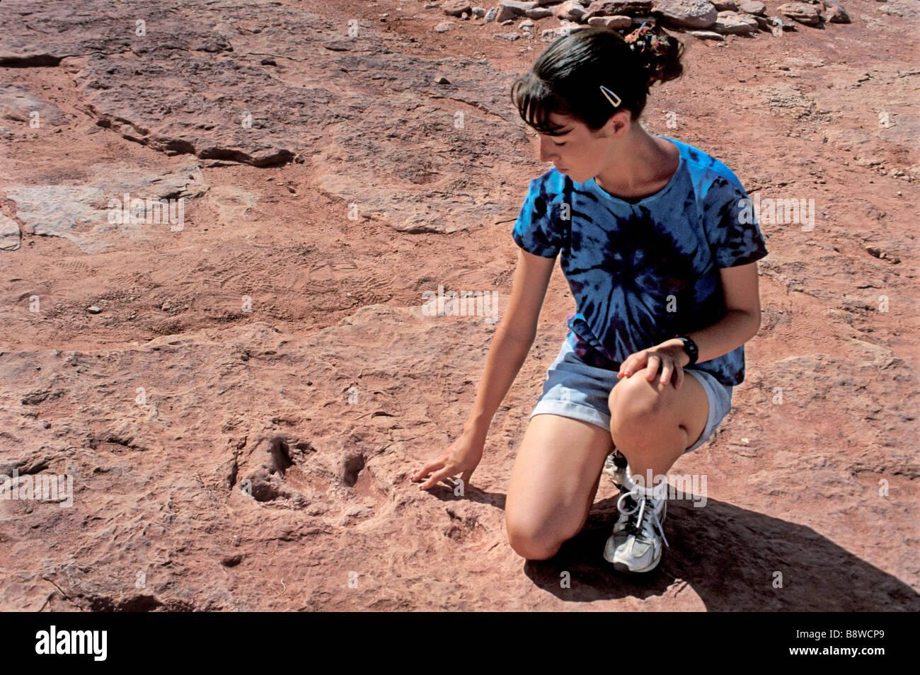 Teenage girl looking at fossil dinosaur footprint near Tuba City Arizona - Stock Image