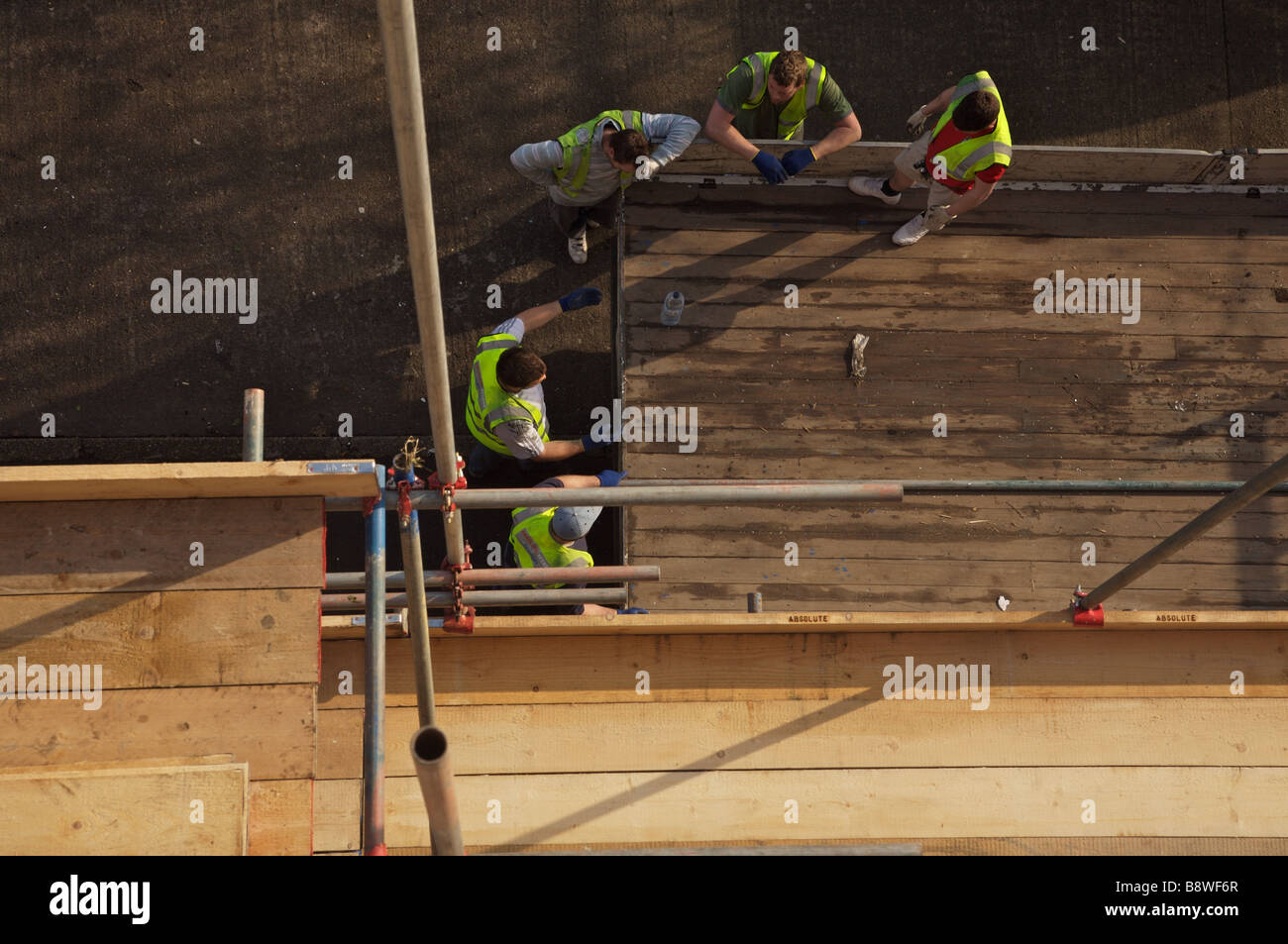 Aerial view of 5 Workmen discussing on a building site, underneath a wooden platform with scaffolding around the - Stock Image