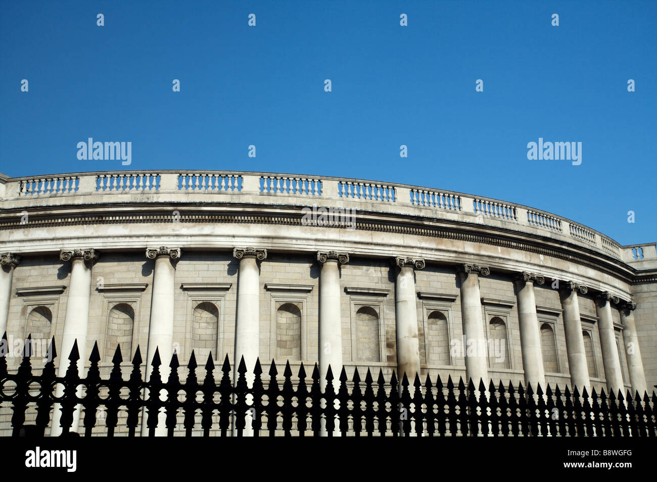 The Bank of Ireland on College Green Dublin Ireland in bright sunshine with a bright blue sky and black railings - Stock Image