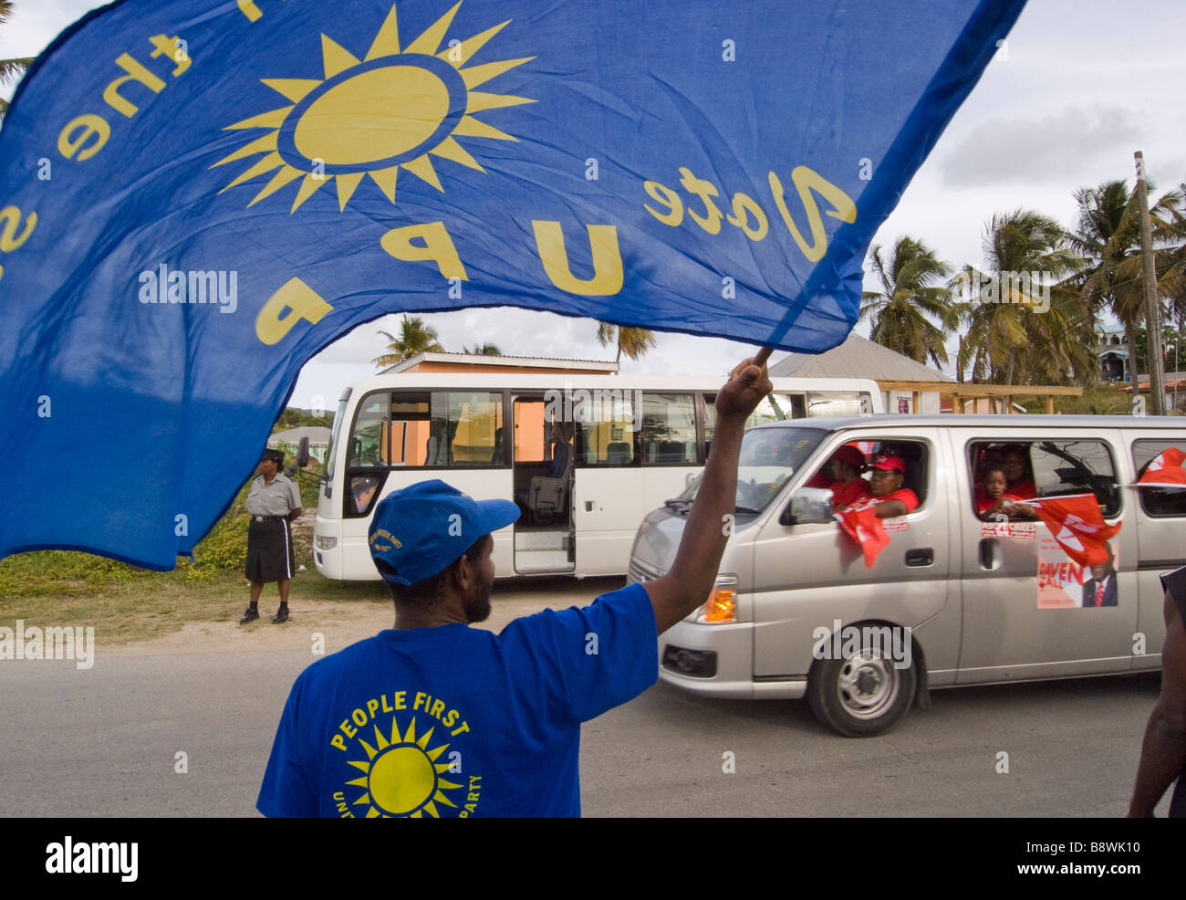 A United Progressive Party UPP supporter waves his flag at Antigua Labour Party supporters on their way to a party - Stock Image