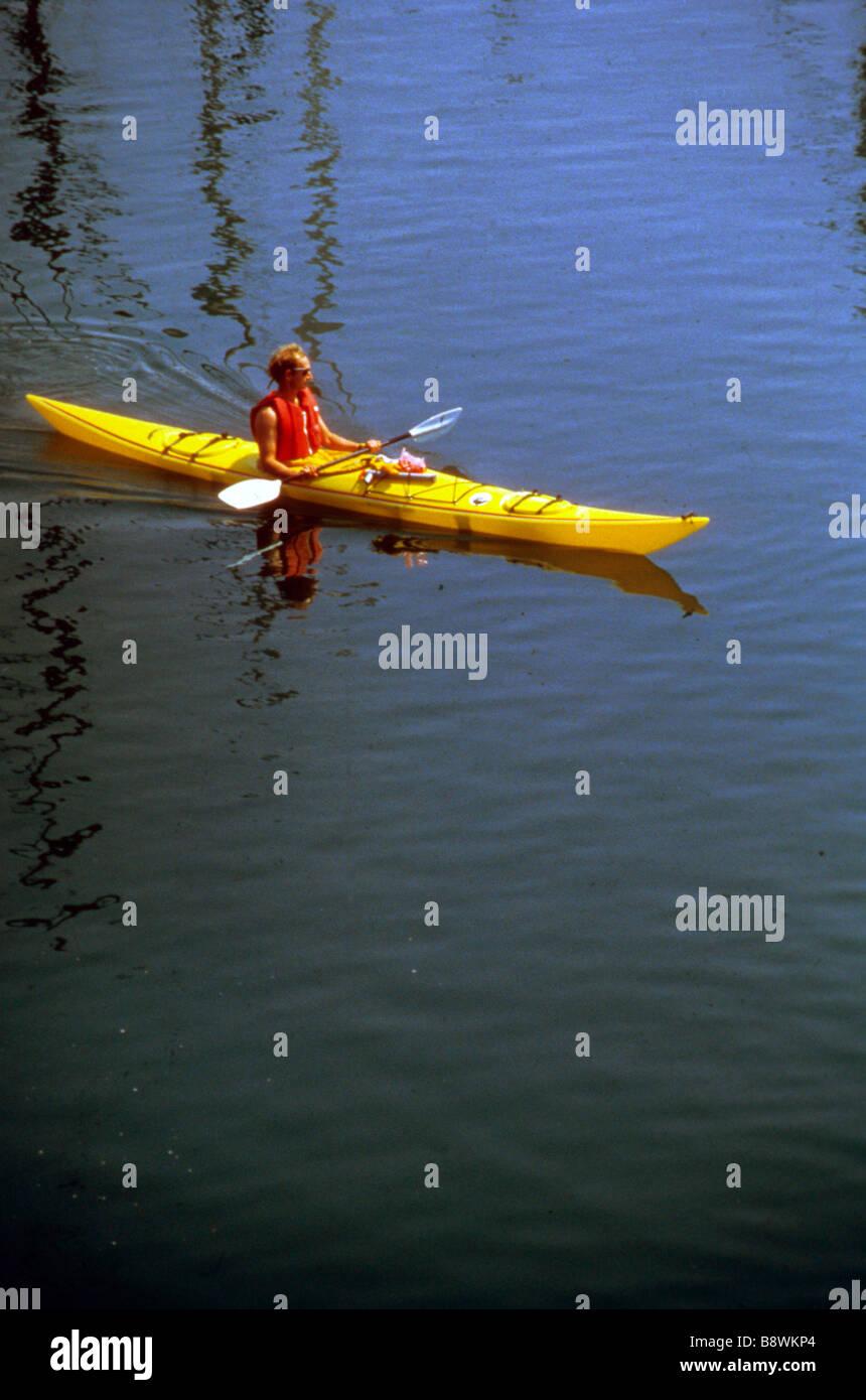 man paddle kayak water calm lake surface wet yellow boat