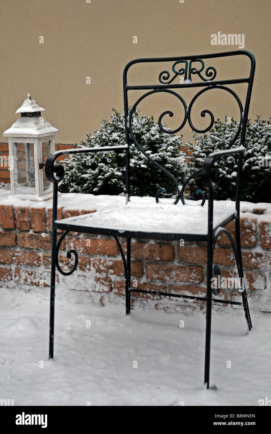 rustic wrought iron garden seat and one light lamp lantern cover covered with snow winter wonderland - Stock Image