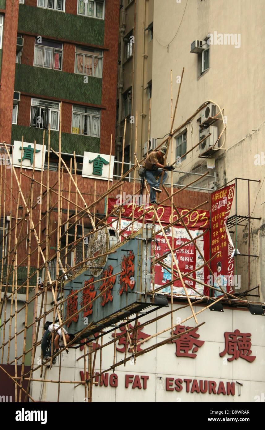 Workers constructing bamboo scaffolding around sign Hong Kong  April 2008 - Stock Image