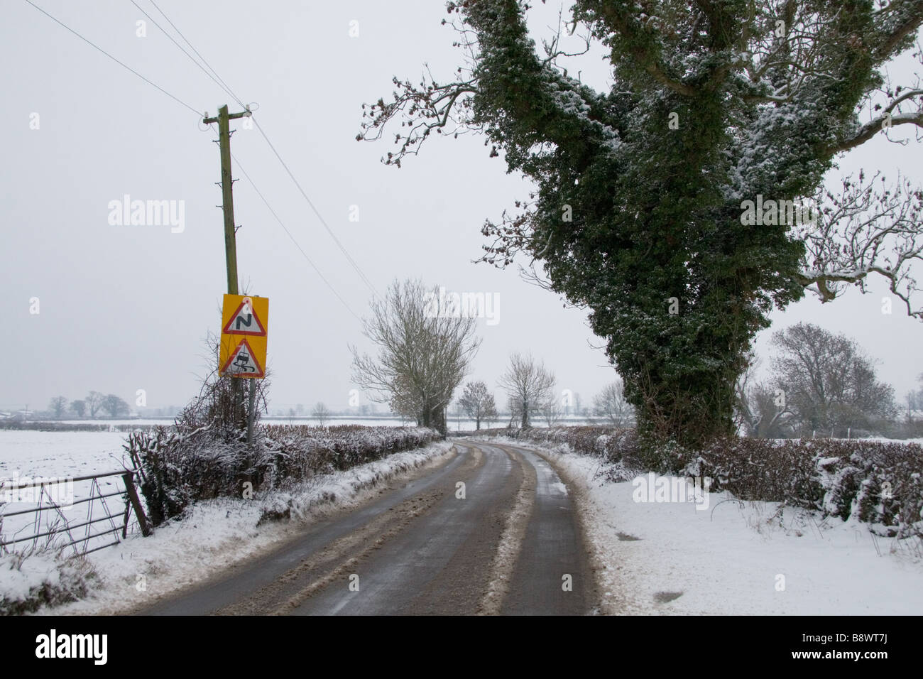 A snowy minor road with slippery surface sign: Somerset, England, UK - Stock Image
