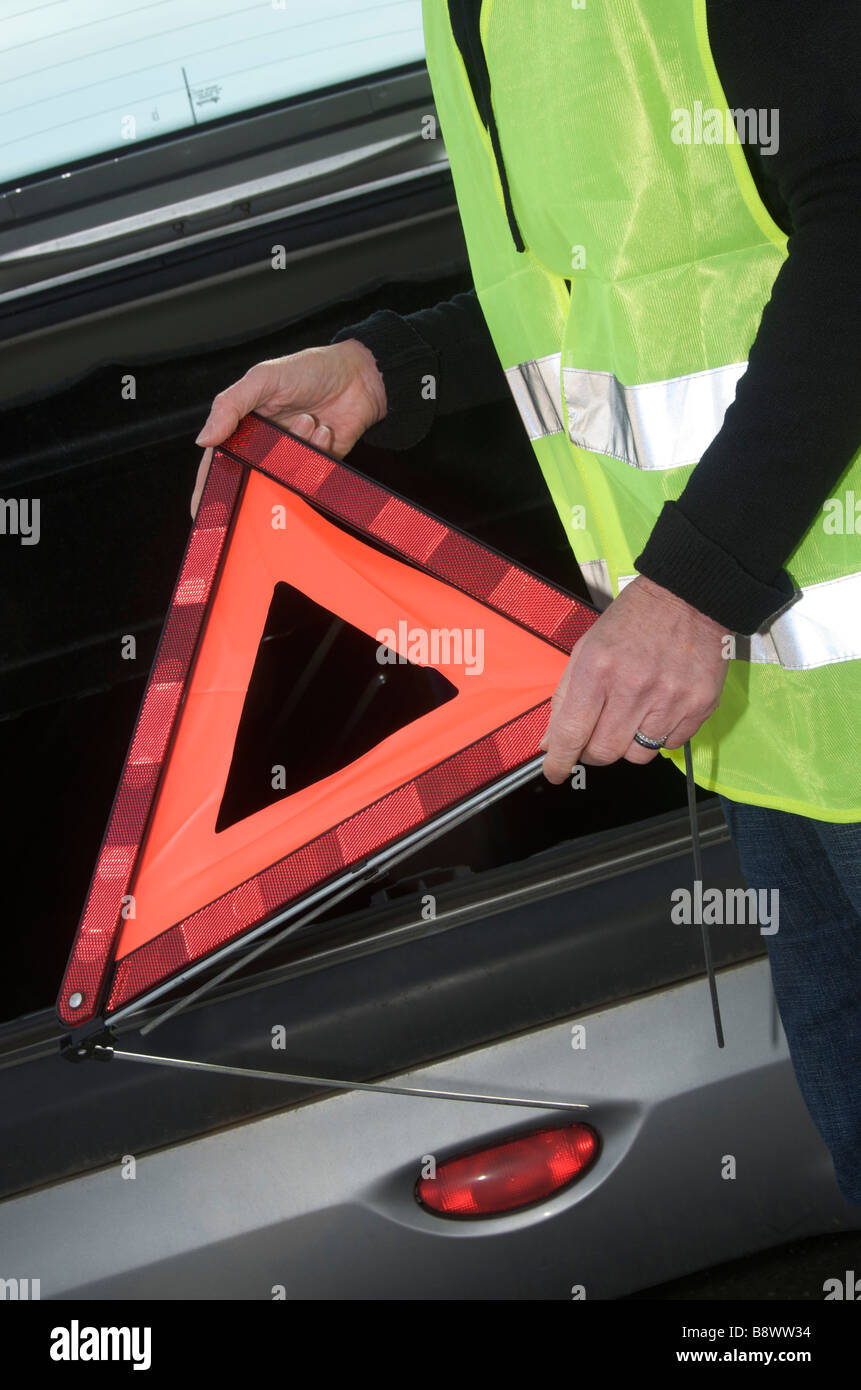 Woman getting a red warning triangle out of her broken down car on the roadside - Stock Image