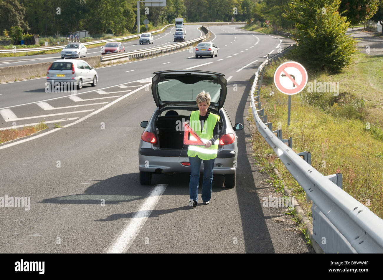 Woman placing her red warning triangle sign behind her broken down car on a slip road onto a French autoroute - Stock Image