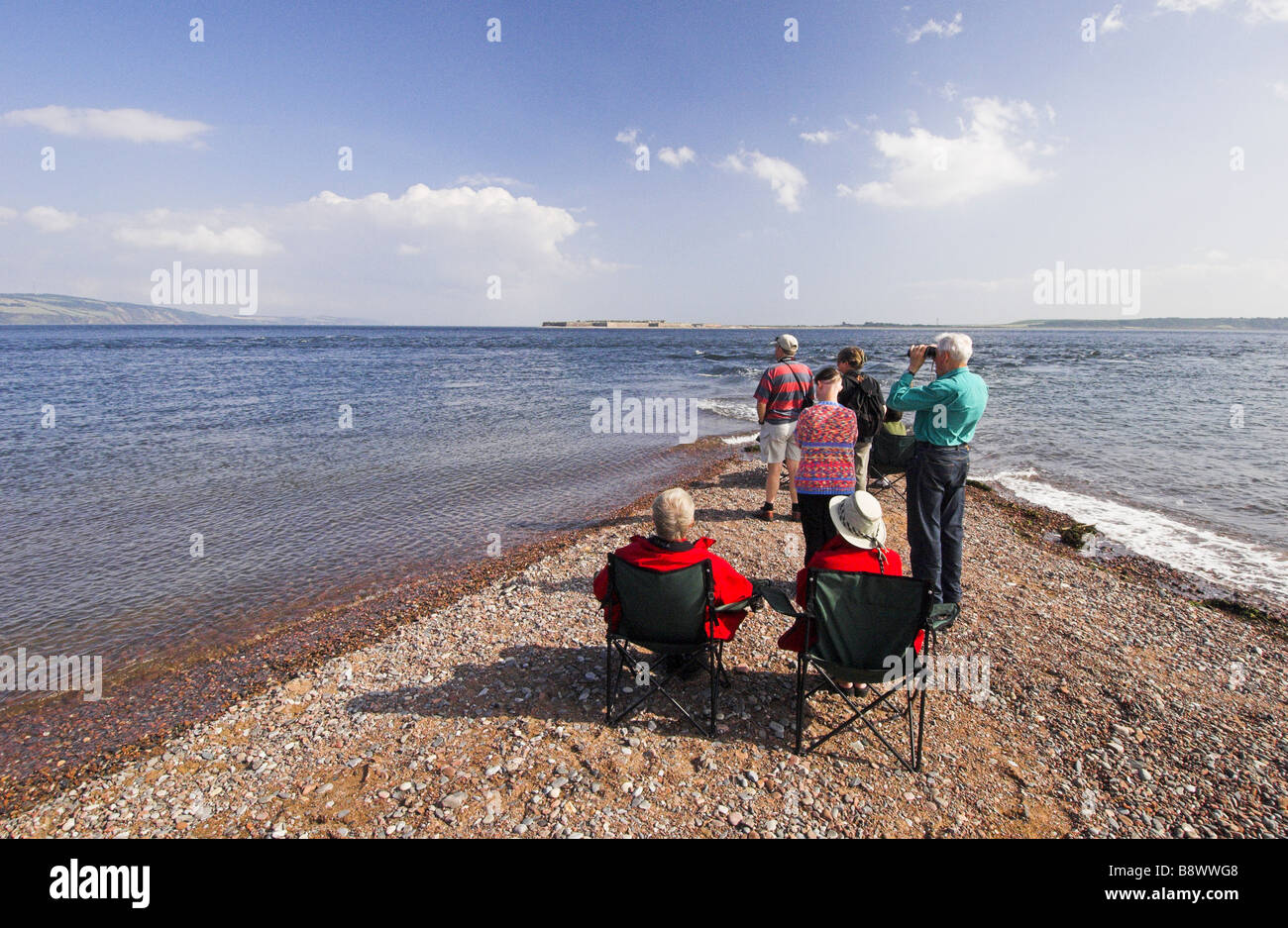 People dolphin-watching from Chanonry Point on the Moray Firth, Scotland. - Stock Image