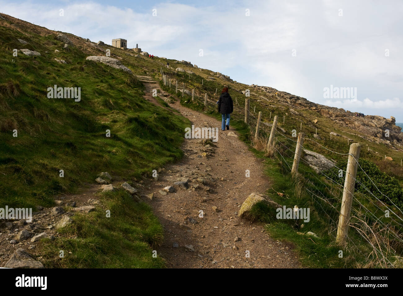 A walker on the path leading up to the old Coastguard Lookout station at Sennen in Cornwall. - Stock Image