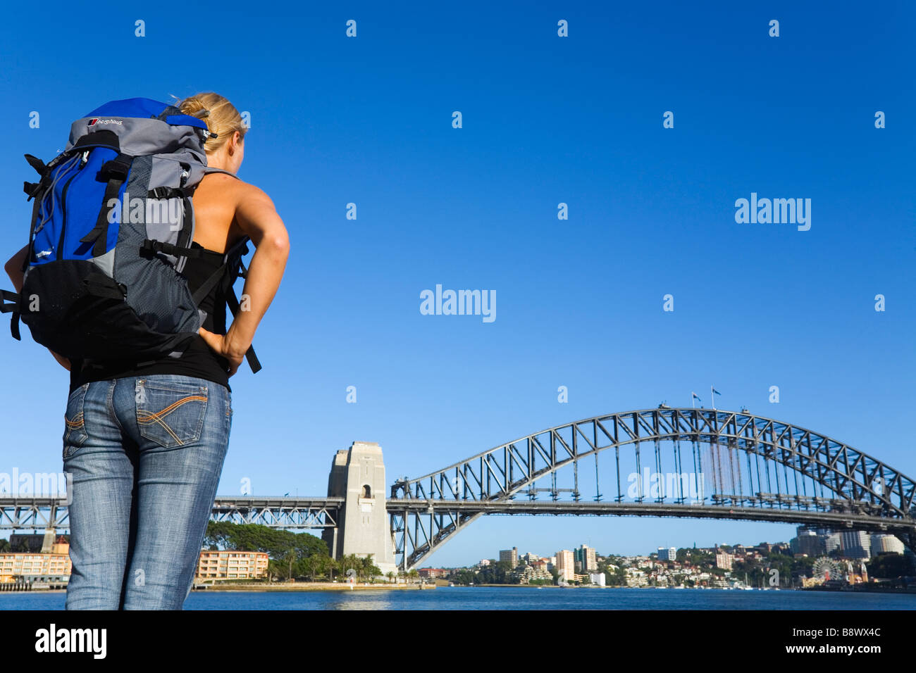 A backpacker looks across Sydney Cove to the Harbour Bridge.  Sydney, New South Wales, AUSTRALIA - Stock Image