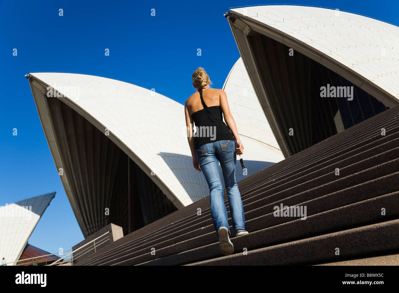 A tourist climbs the steps of the Sydney Opera House.  Sydney, New South Wales, AUSTRALIA - Stock Image