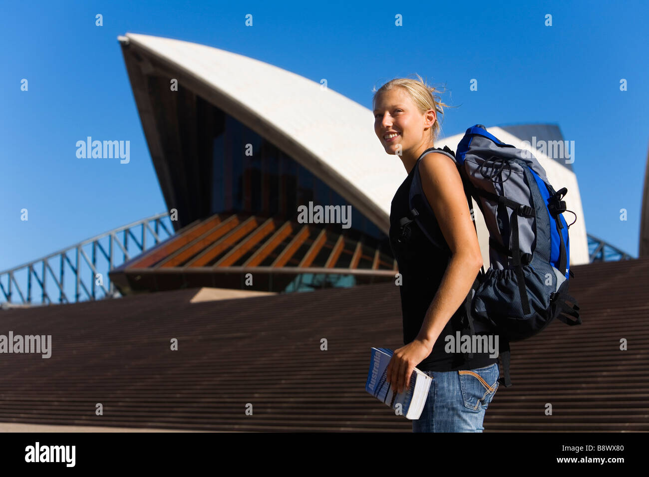 Young backpacker with guide book standing in front of the Sydney Opera House, Sydney, New South Wales, AUSTRALIA. - Stock Image