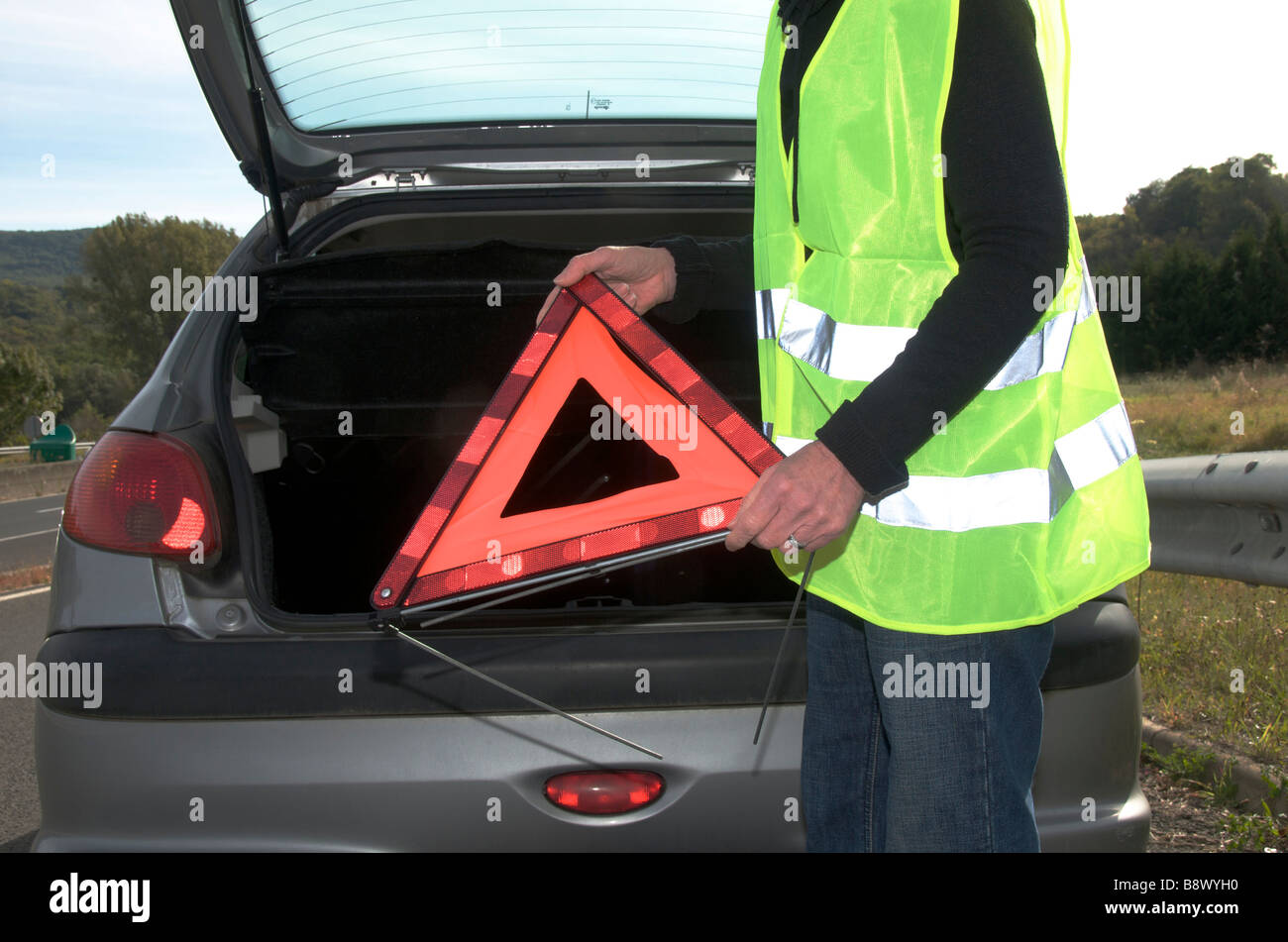 Woman getting red warning triangle out of her broken down car - Stock Image