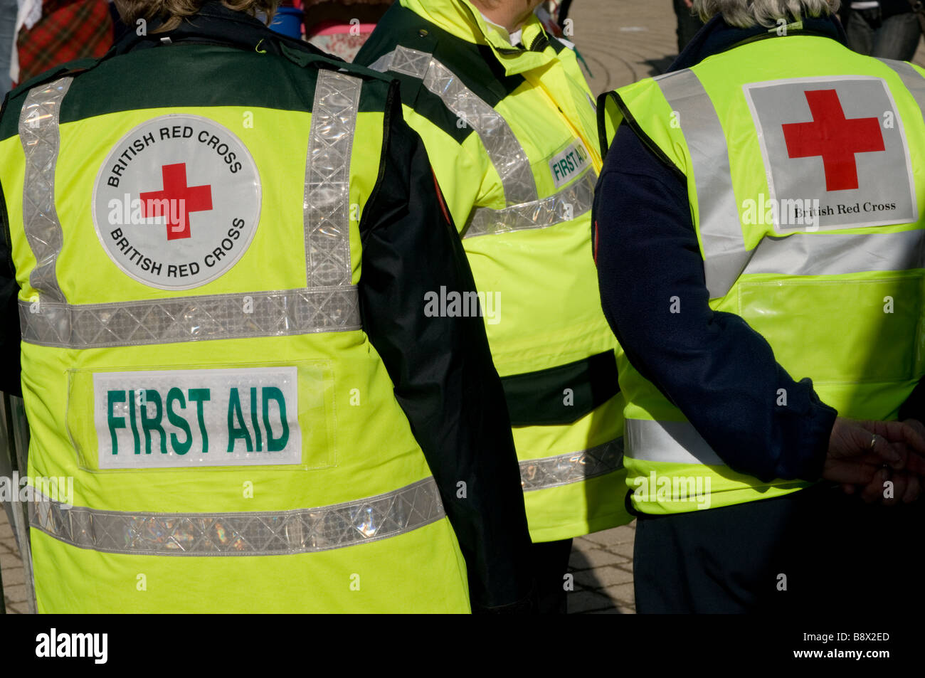 rear view of three First aid volunteer British Red Cross workers wearing high visibility yellow jackets, UK - Stock Image