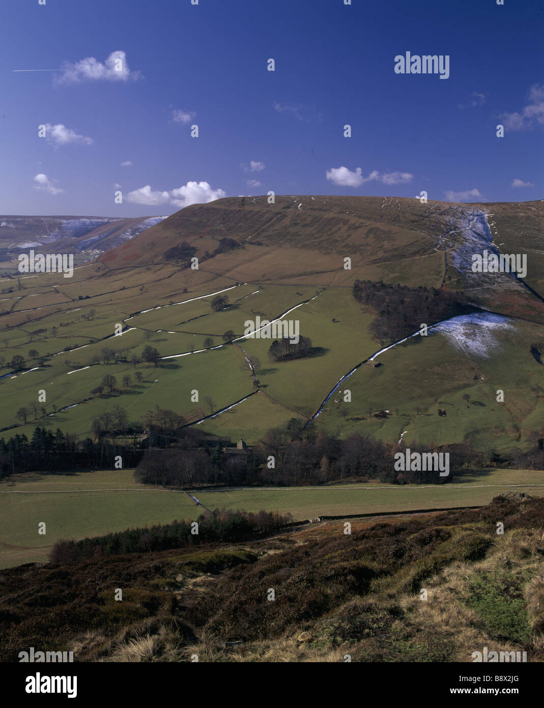 A view of Edale in early spring snow dusts the side of the hills in shade - Stock Image