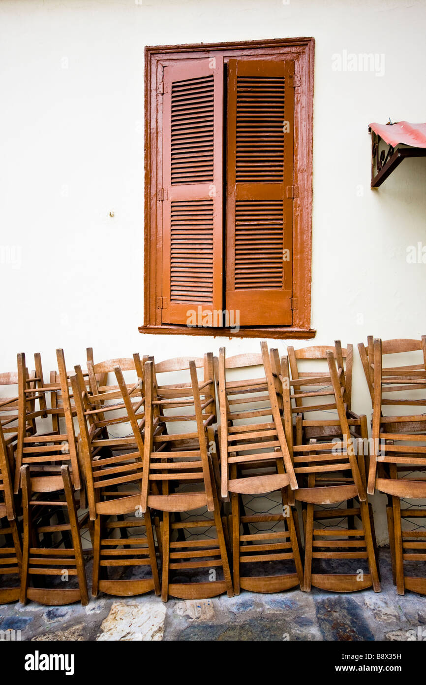 Chairs stacked up against a wall under the window of the cafe they ...