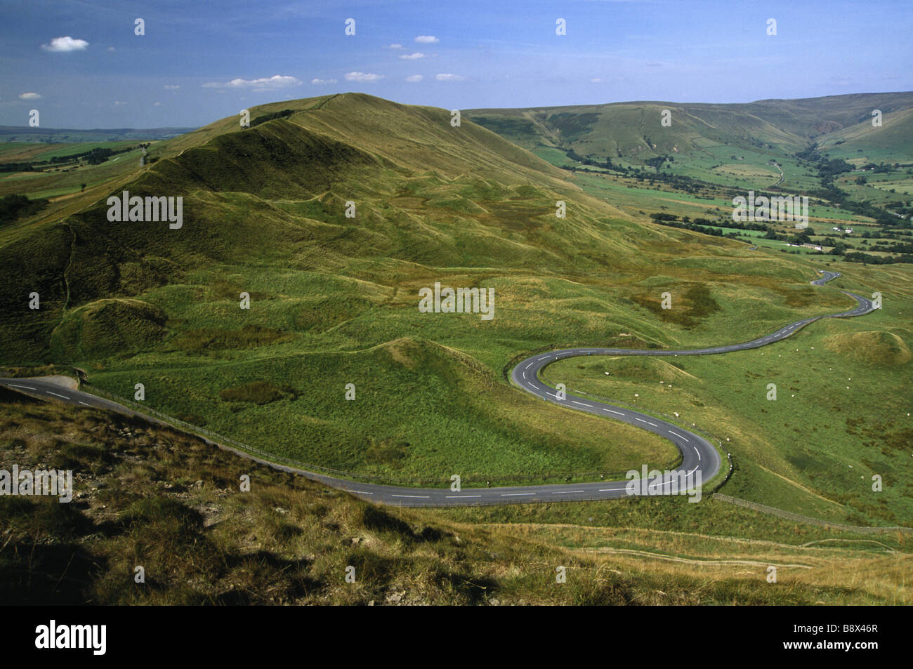 A view of Rushup Edge from Mam Tor in the Peak District with a road winding at the bottom of the hill - Stock Image