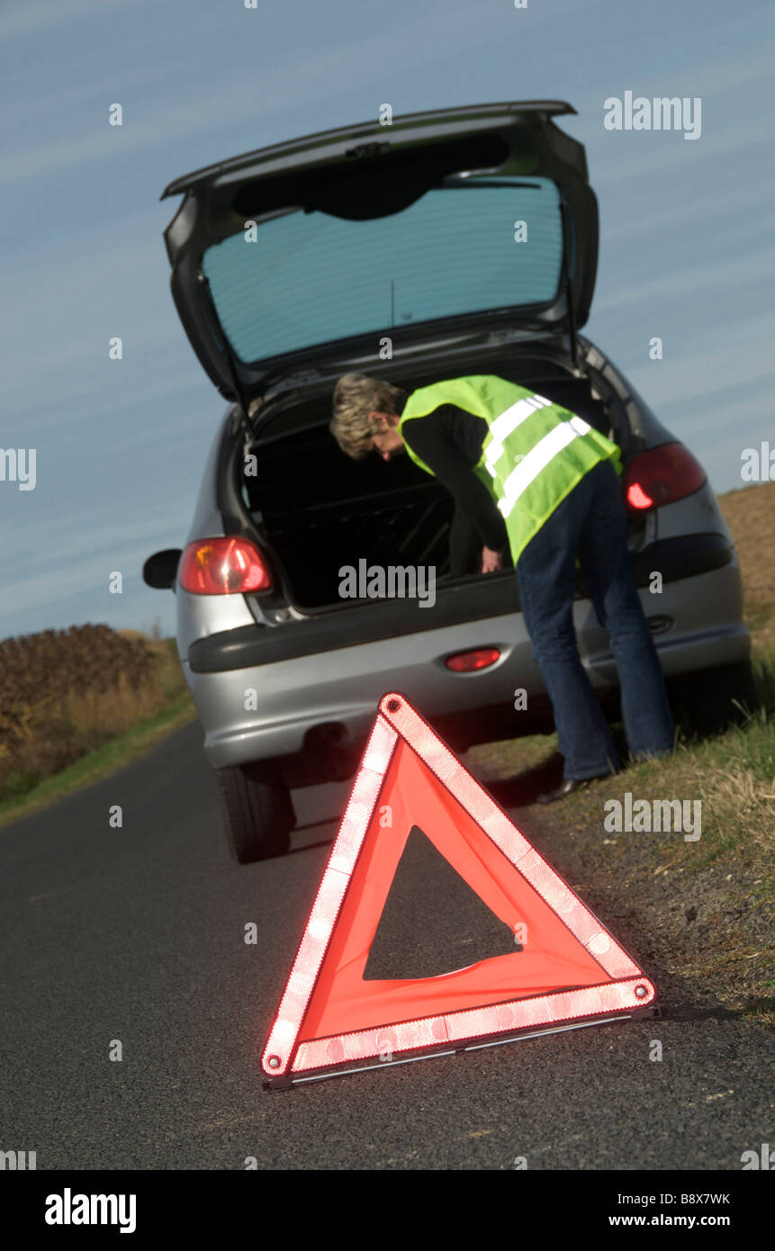 Woman with her broken down car parked at the roadside wearing yellow high visibility / hi viz jacket and warning Stock Photo