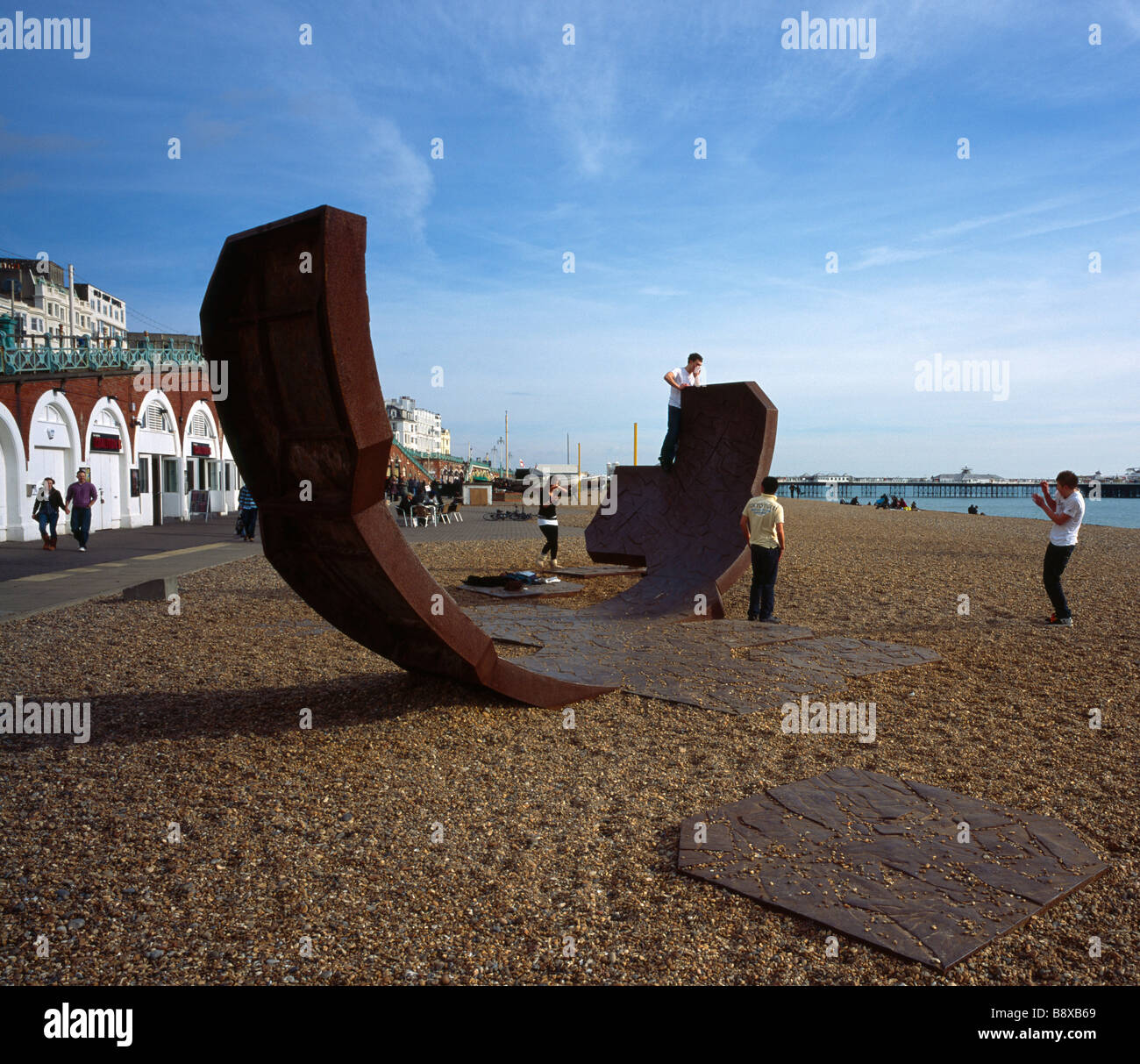Teenagers playing on a modern art sculpture called Passacaglia. Brighton Beach, Sussex, England, UK. Stock Photo