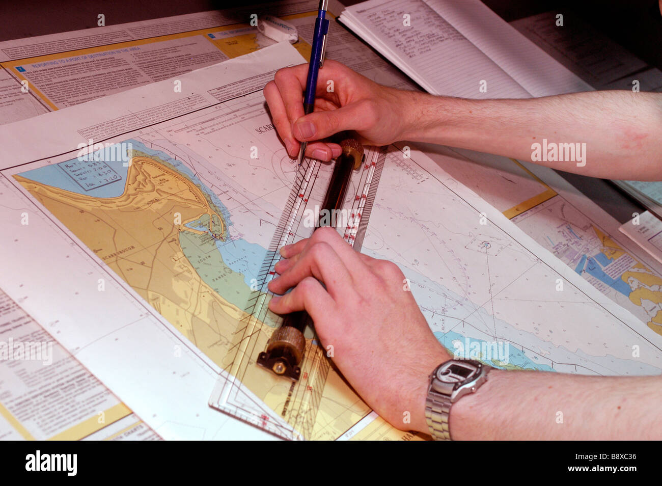 An officer of the Royal Fleet Auxiliary plots the ship s position on a nautical chart on the bridge of the RFA Wave - Stock Image