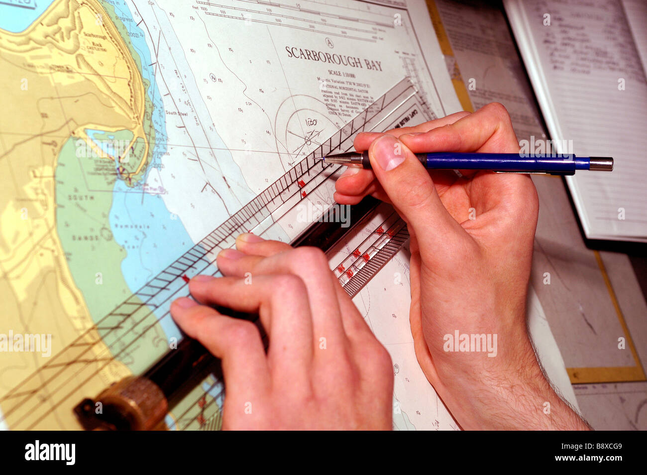An officer of the Royal Fleet Auxiliary plots the ship's position on a nautical chart on the bridge of the RFA - Stock Image