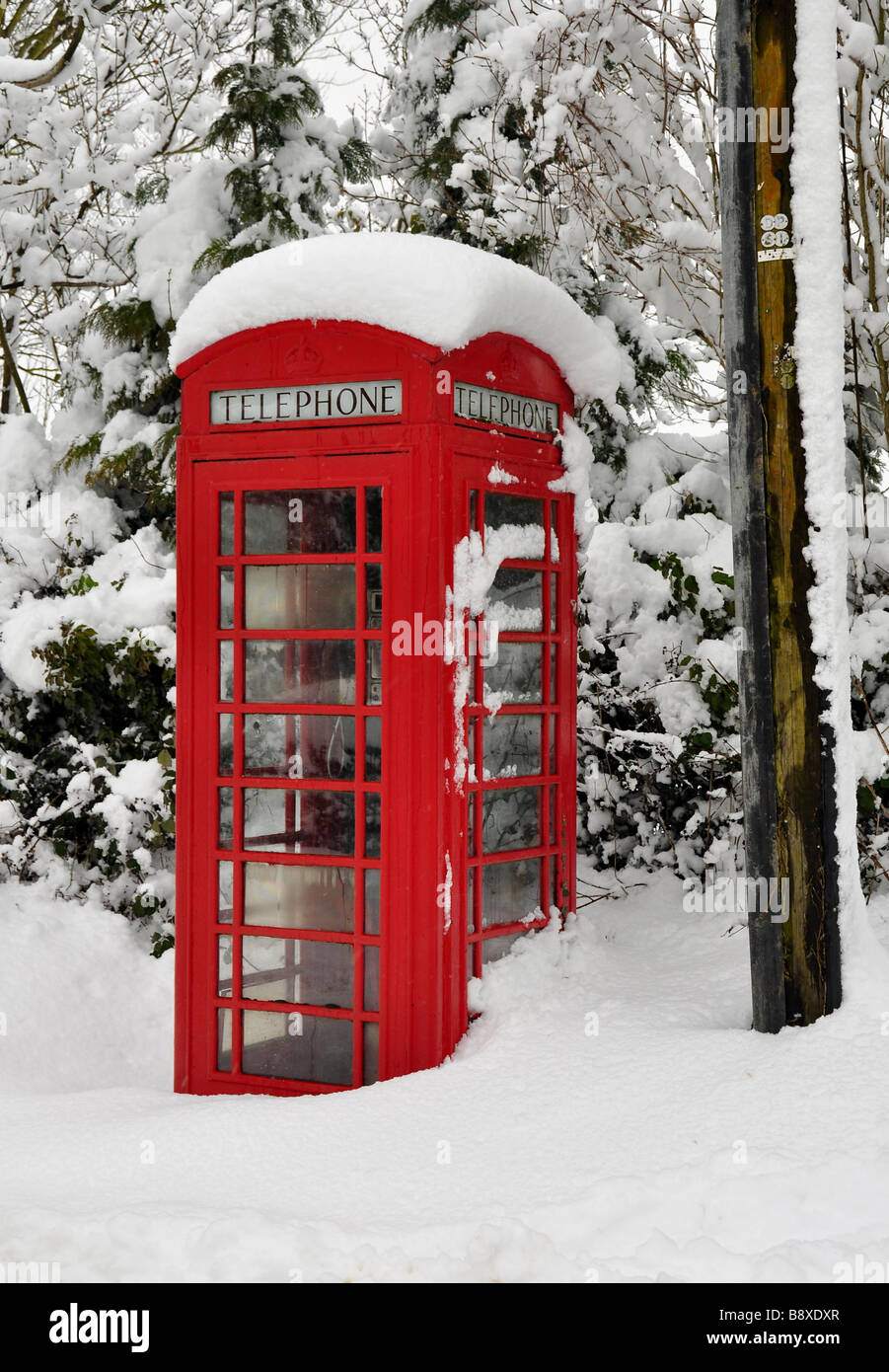 Old rural telephone box covered in deep snow - Stock Image