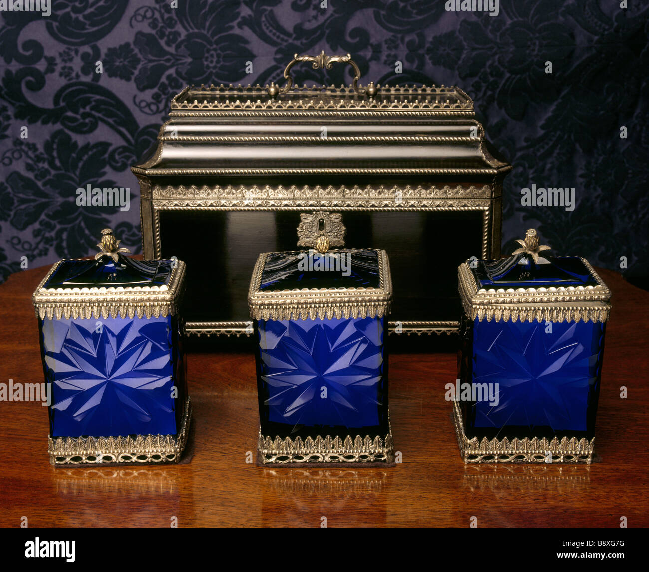 A set of three blue glass Tea Caddies and covers mounted in silver ebony case behind mid C18th Stock Photo
