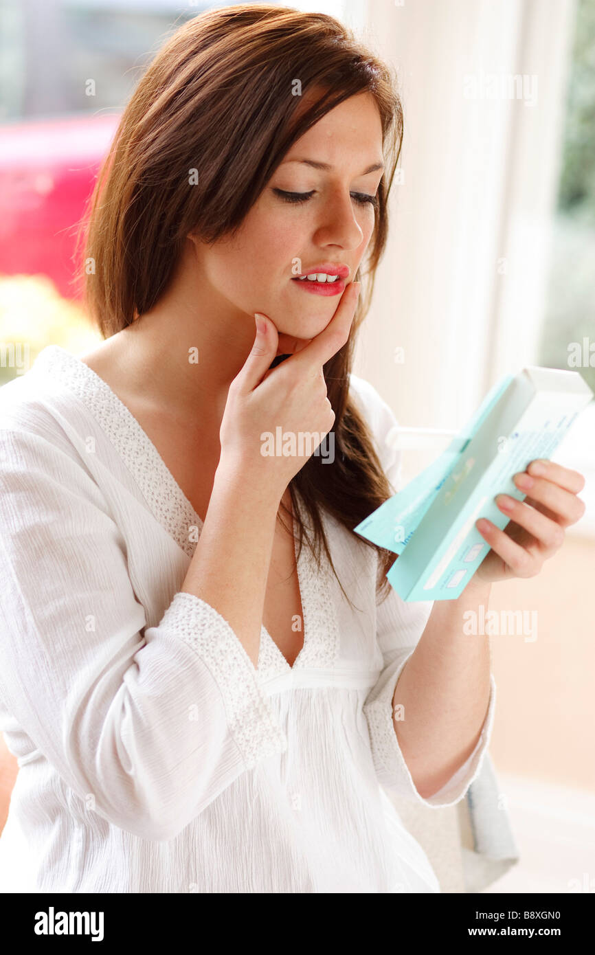 Woman looking at results of pregnancy test - Stock Image