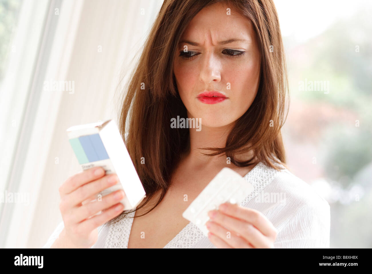 Woman looking at medication - Stock Image