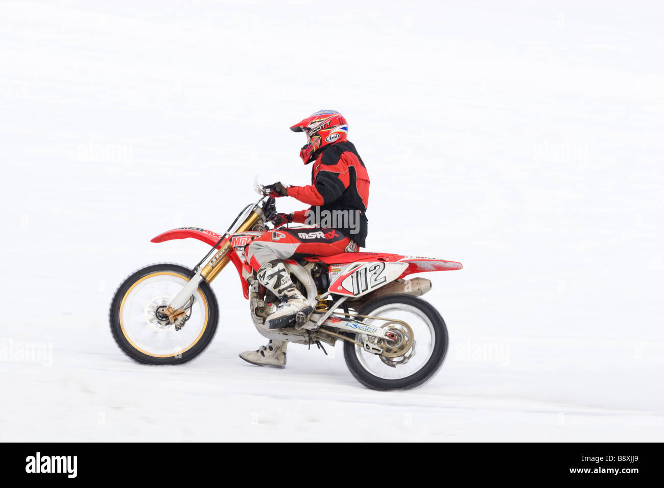 Winter races of motorcyclists It is photographed on a white background of snow - Stock Image