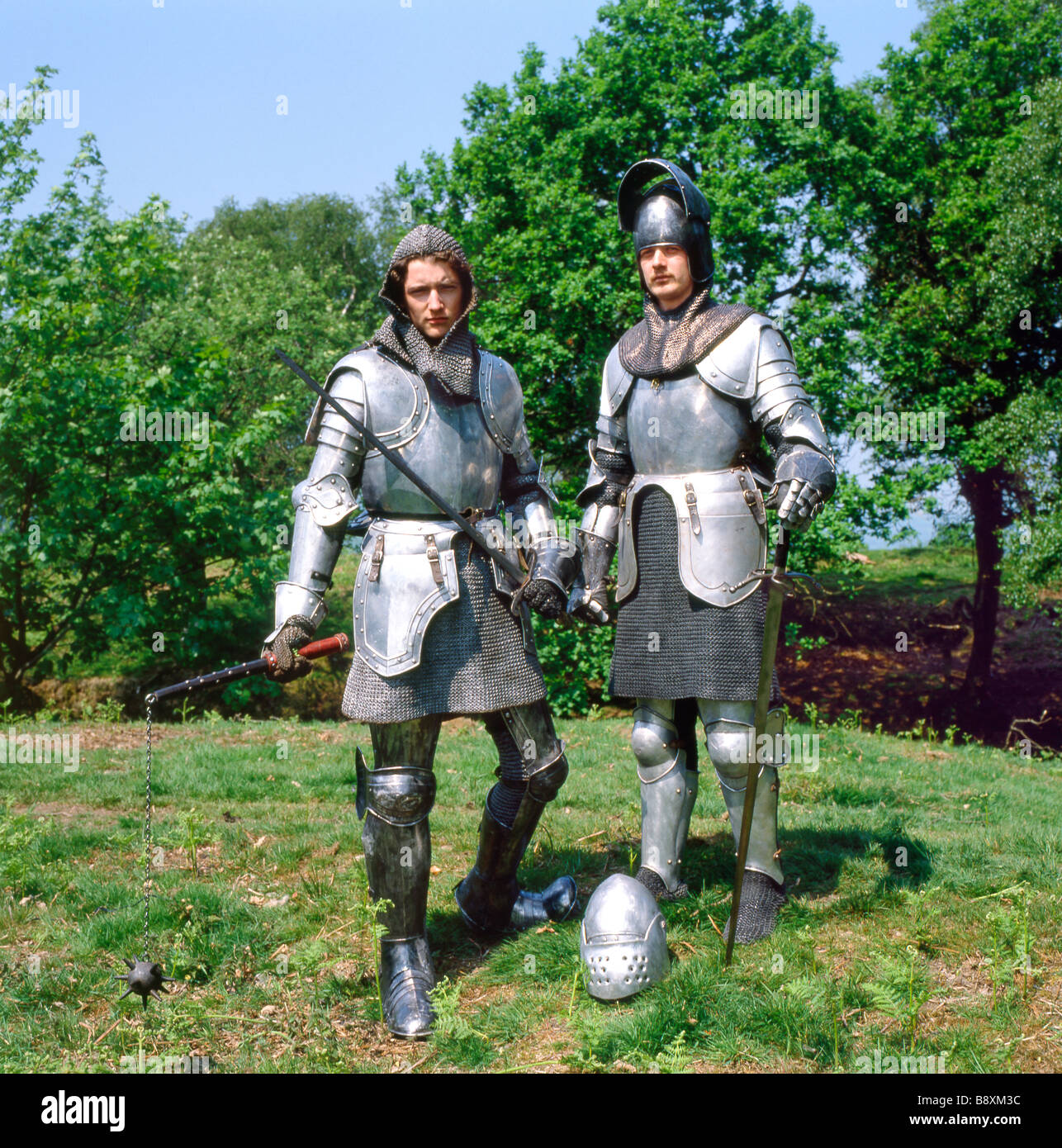 Medieval knights in shining armour historical costume posing for portrait wearing chainmail, helmets and swords - Stock Image
