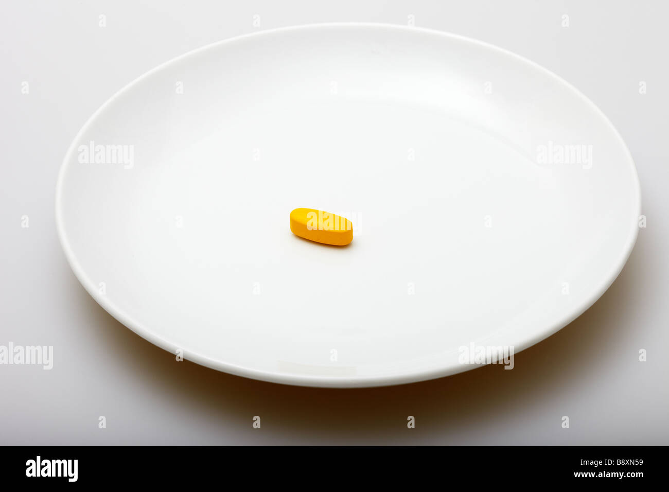 Vitamin Pill on White Plate - Stock Image