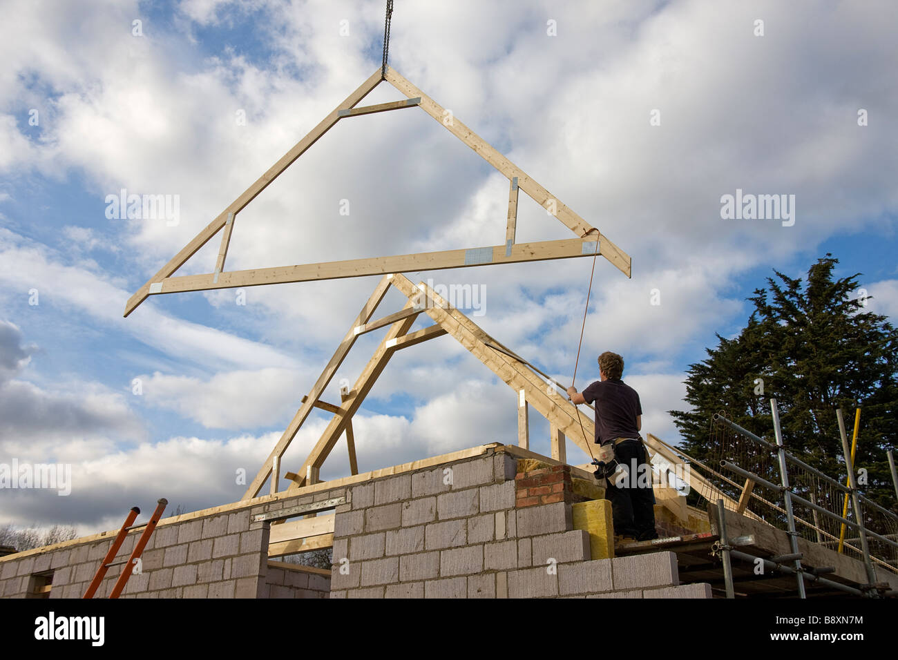 Timber attic roofing truss being lowered into position on roof of new house. - Stock Image