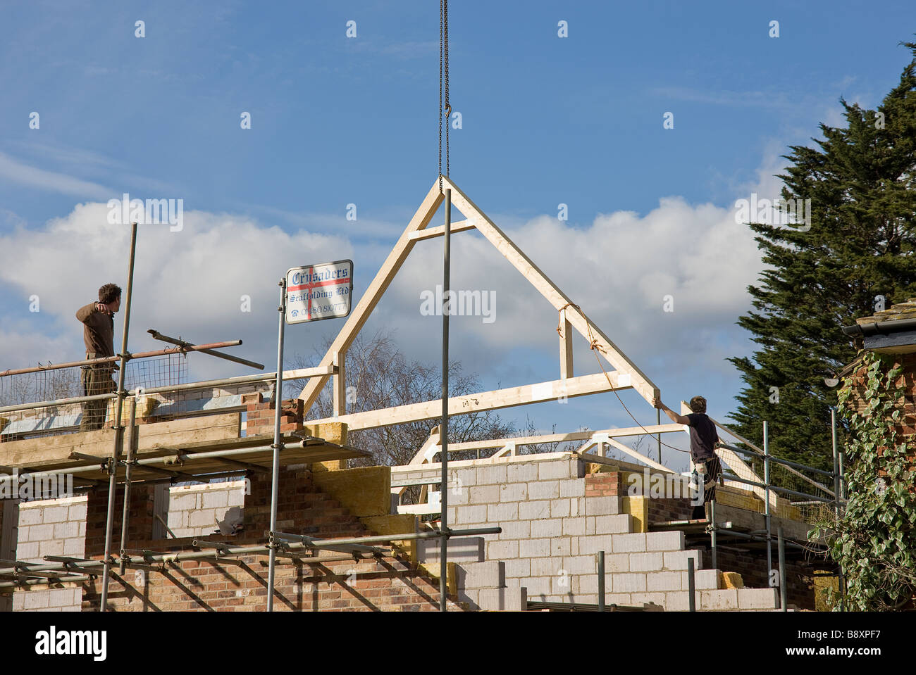 The first main roof attic truss being lowered into correct position ready to start building the roof for new house - Stock Image