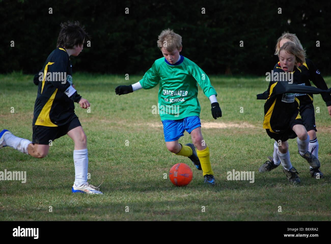 young boys playing football,uk Stock Photo