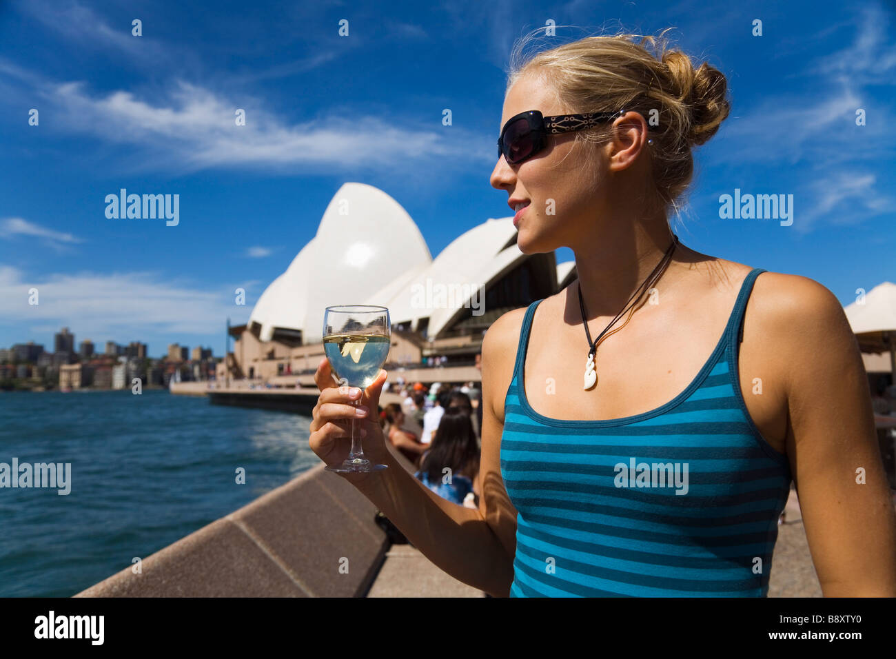 A woman enjoys a drink at the Opera Bar on Sydney harbour.  Sydney, New South Wales, AUSTRALIA - Stock Image