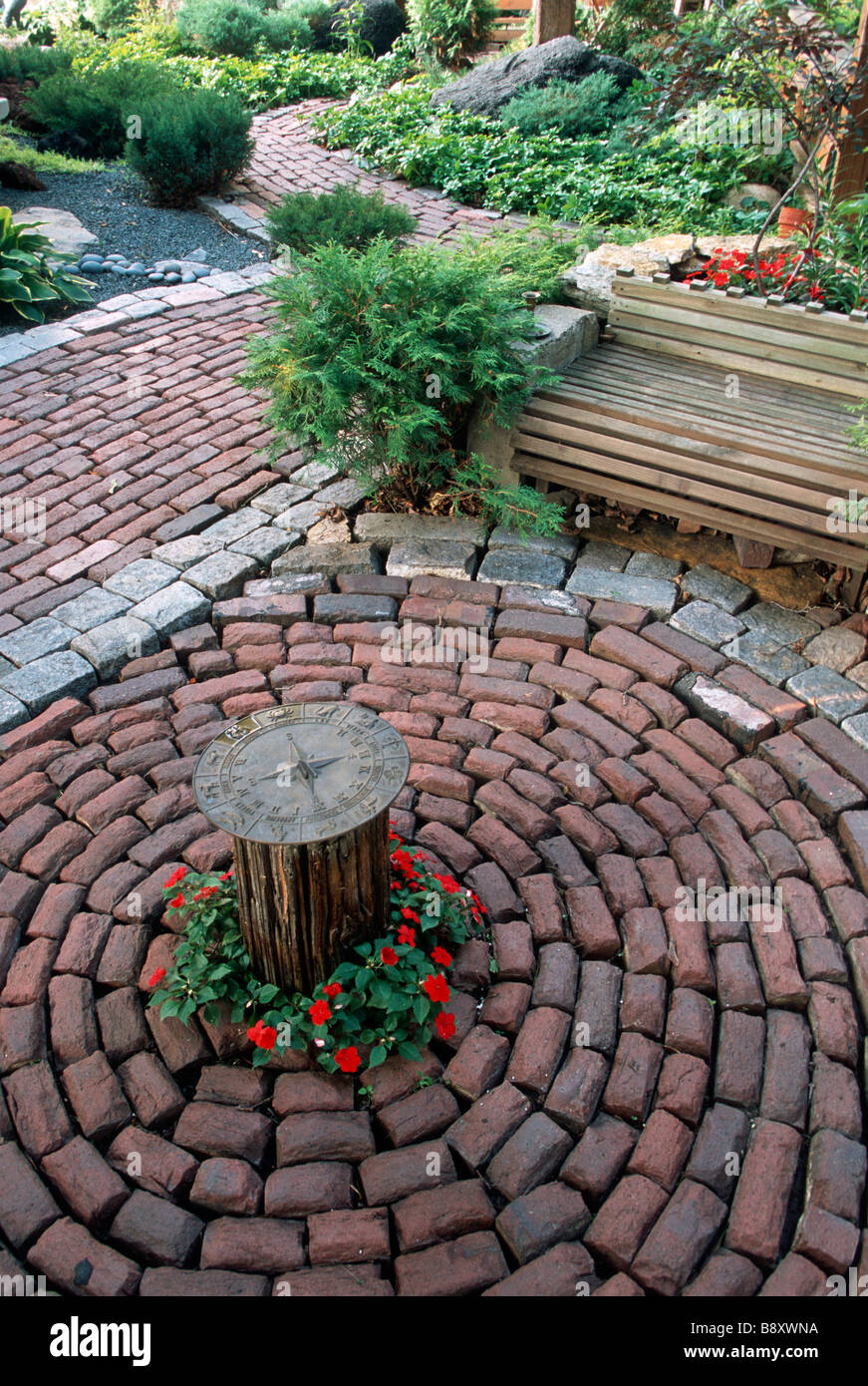 SALVAGED STONE STREET PAVERS USED IN MINNEAPOLIS, MINNESOTA GARDEN WITH  SUNDIAL. SUMMER.