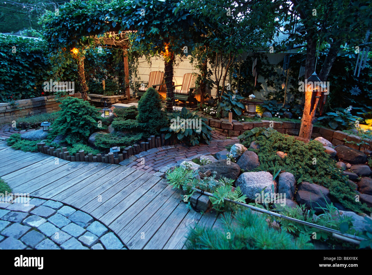 JAPANESE INSPIRED GARDEN IN MINNESOTA INCLUDES OUTDOOR SEATING AREA WITH  LIGHTS FOR EVENING USE.