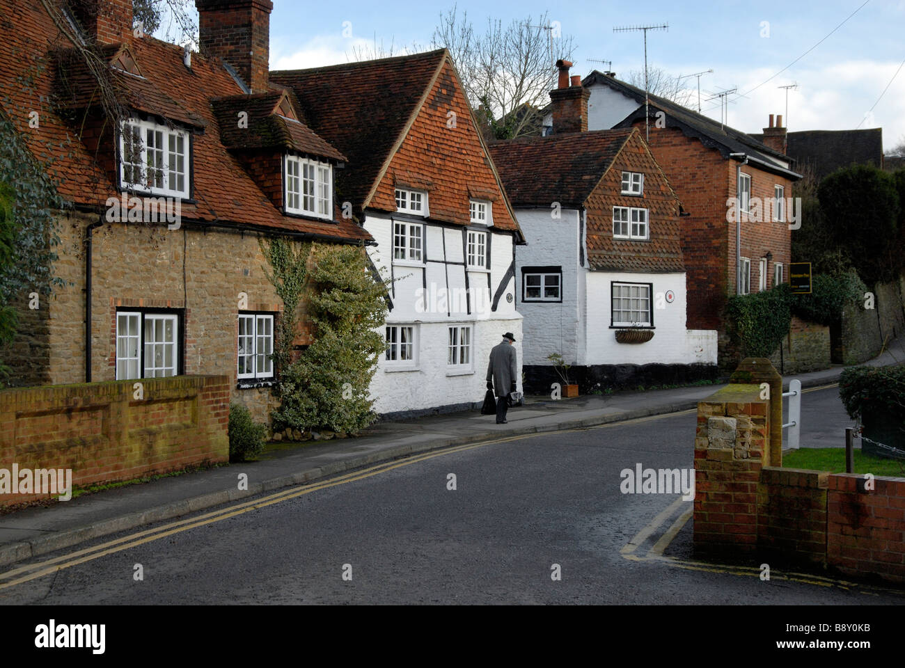 16th and 17th century cottages on Mill Lane with man in long coat and hat walking past, Godalming, Surrey, England - Stock Image