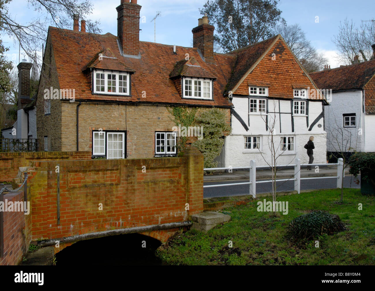 16th and 17th century cottages, bridge over River Ock and young woman walking, Mill Lane, Godalming, Surrey, England - Stock Image