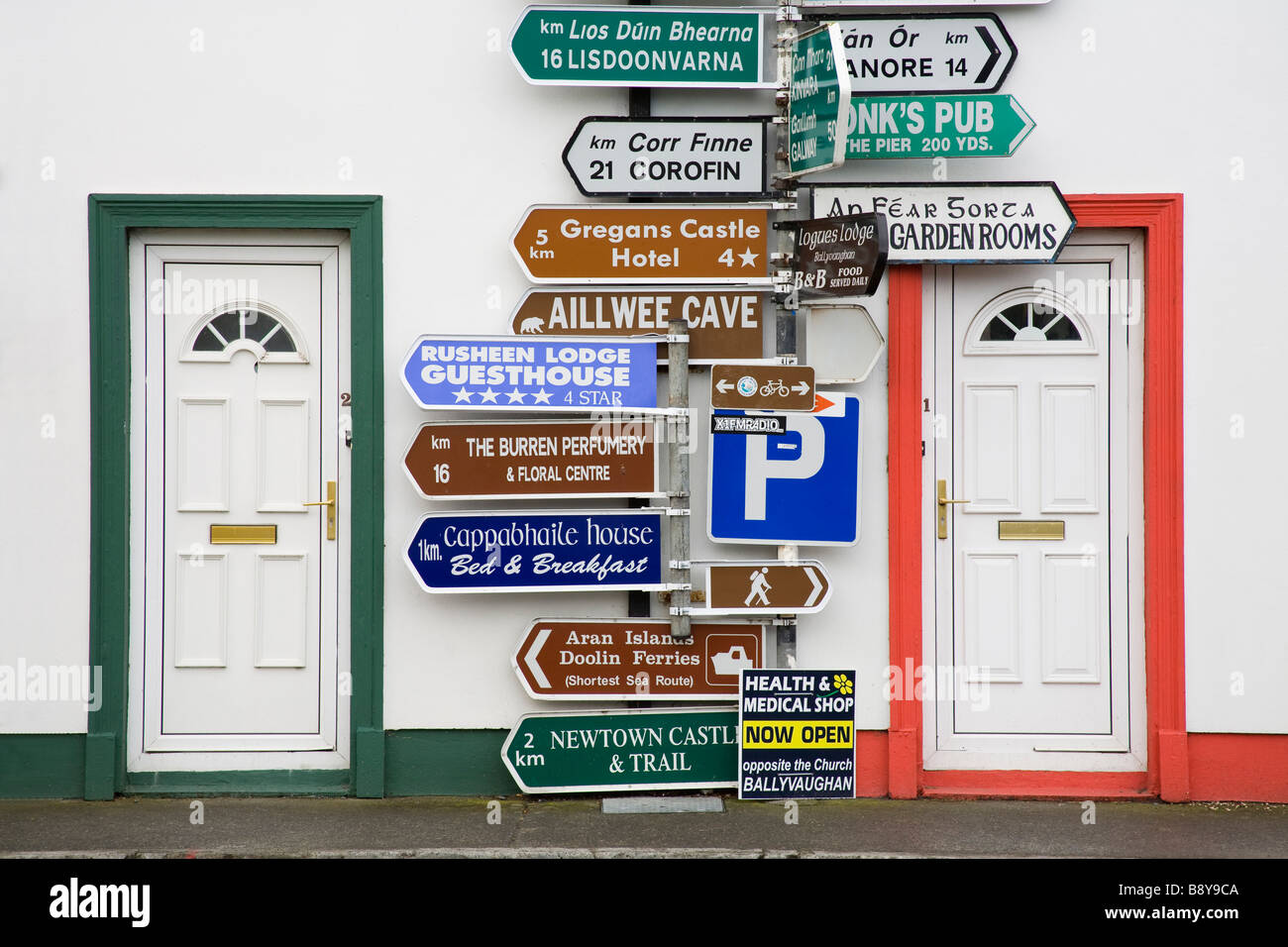 Directional signs in front of a building, Ballyvaughan, The Burren, County Clare, Munster Province, Republic of - Stock Image