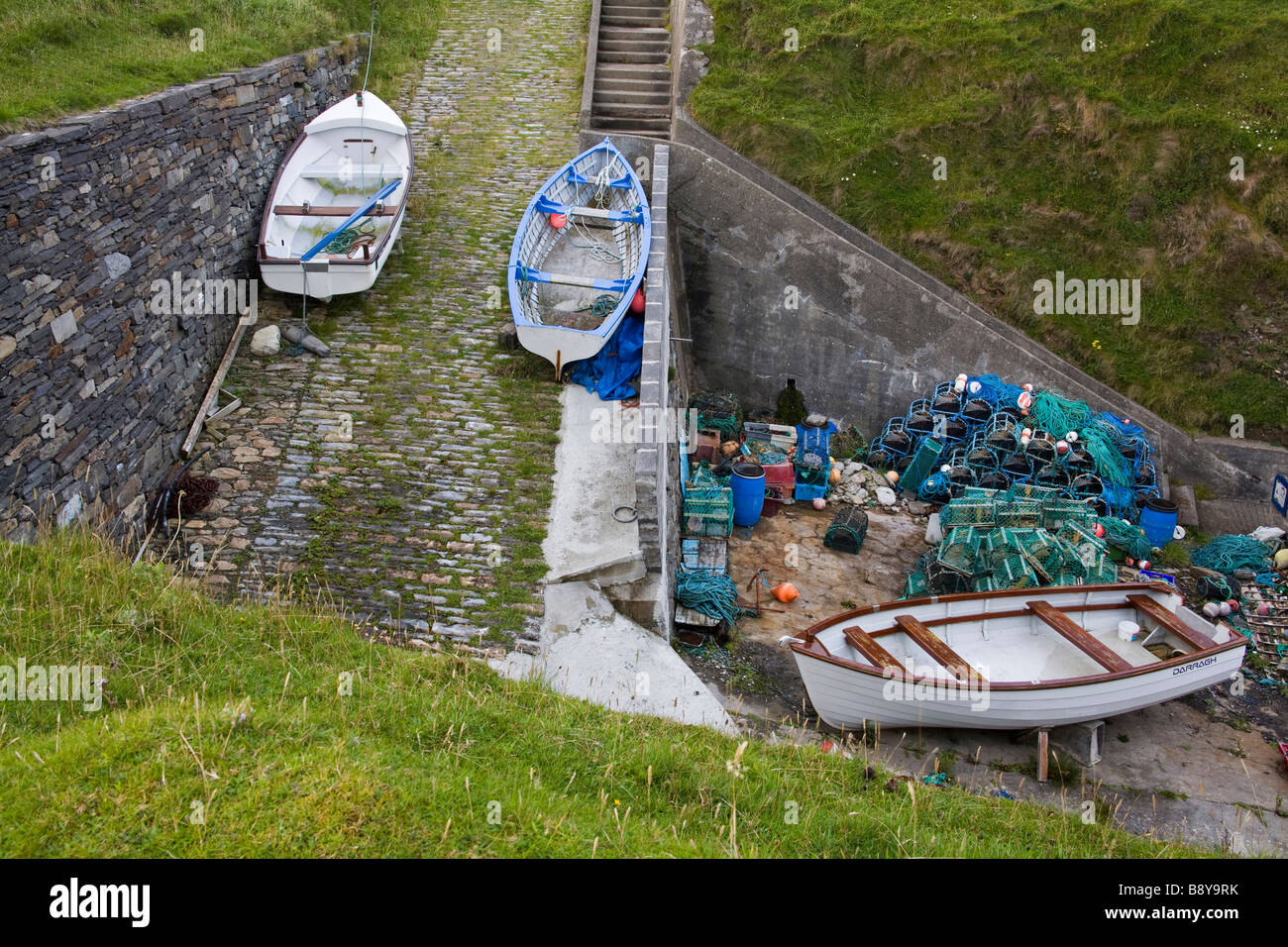 Garbage cans with fishing boats on a pier, Malin Beg, County Donegal, Ulster Province, Ireland - Stock Image