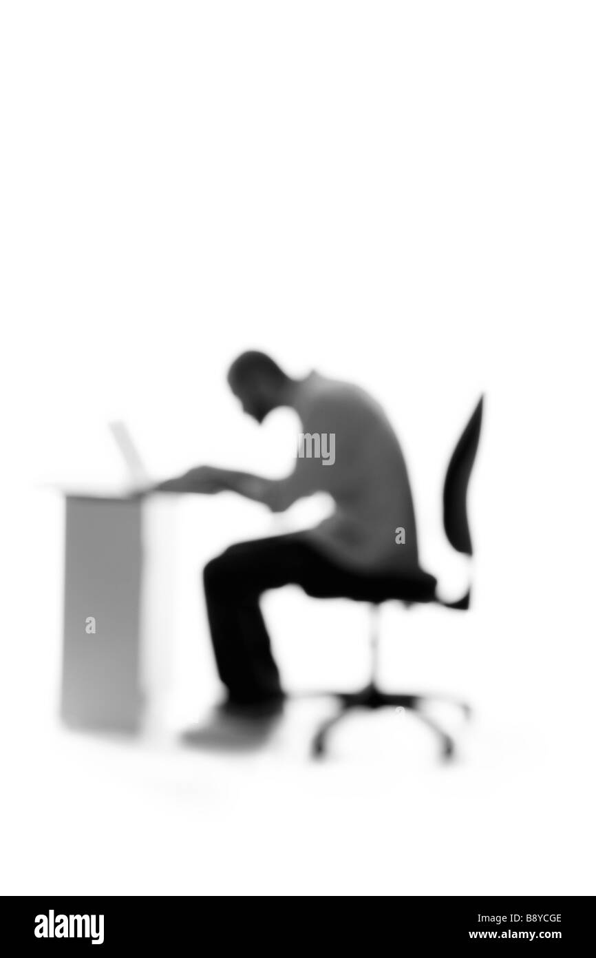 Silhouette of a man sitting by a desk. - Stock Image