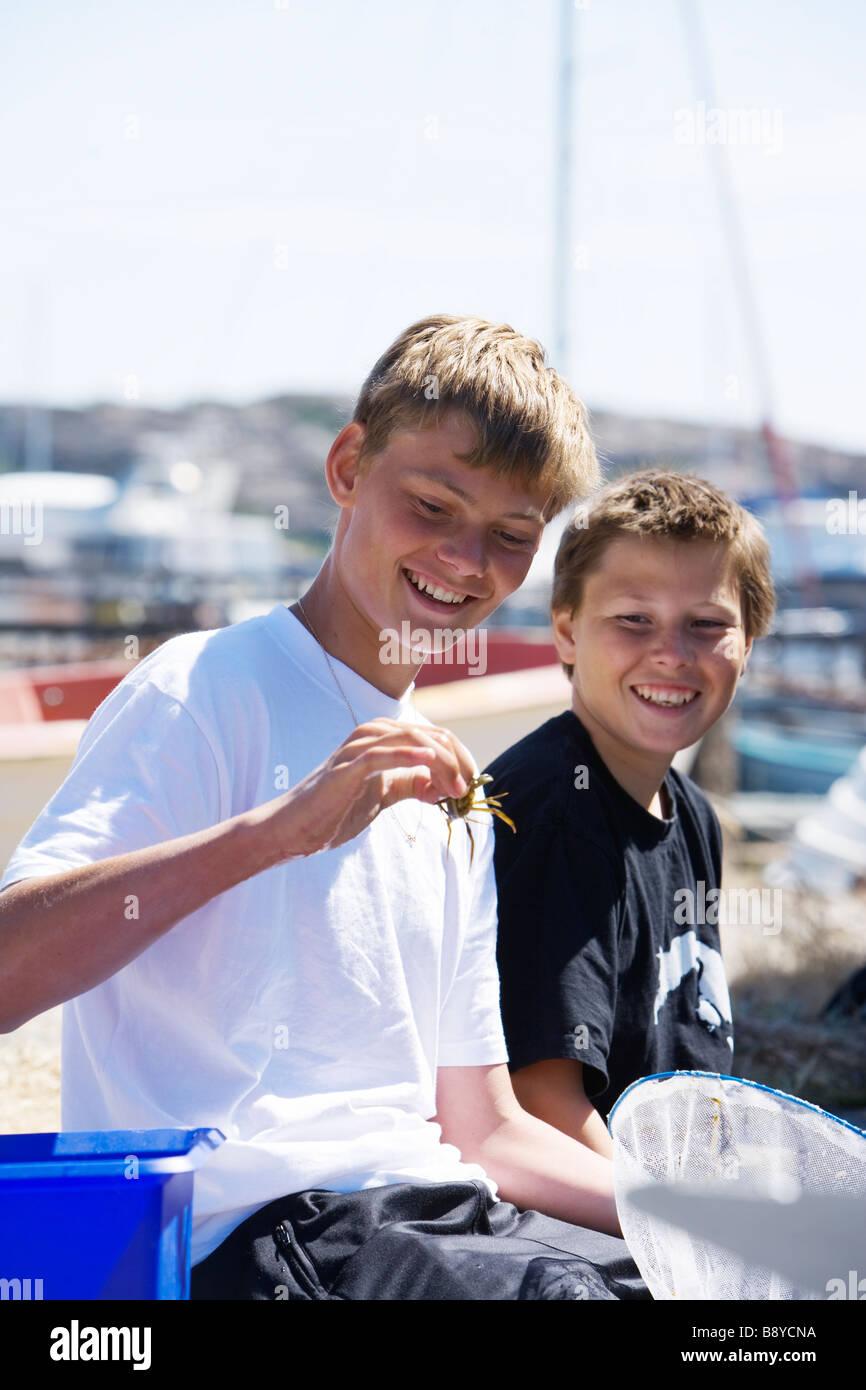 Two boys and a crab Smogen Bohuslan Sweden. - Stock Image