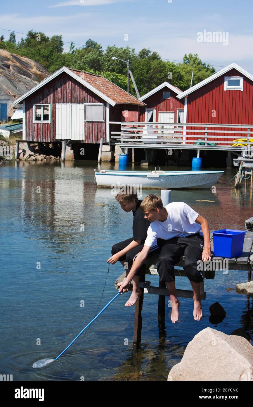 Two boys fishing Smogen Bohuslan Sweden. - Stock Image