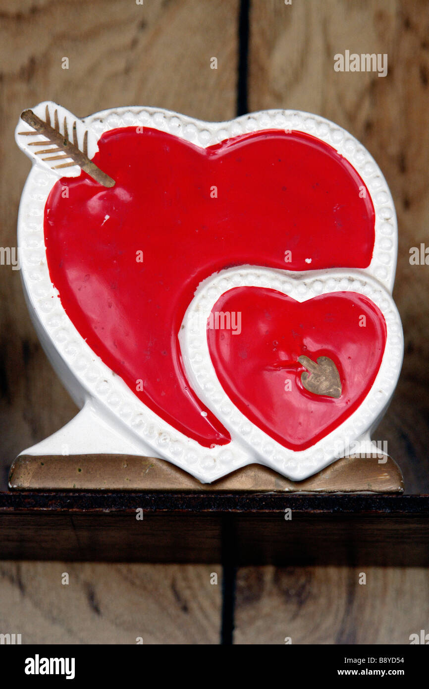 Still Life Photograph of Kitschy Hand Painted Ceramic Decoration of Two 2 Red Hearts and a Gold Arrow It Against - Stock Image