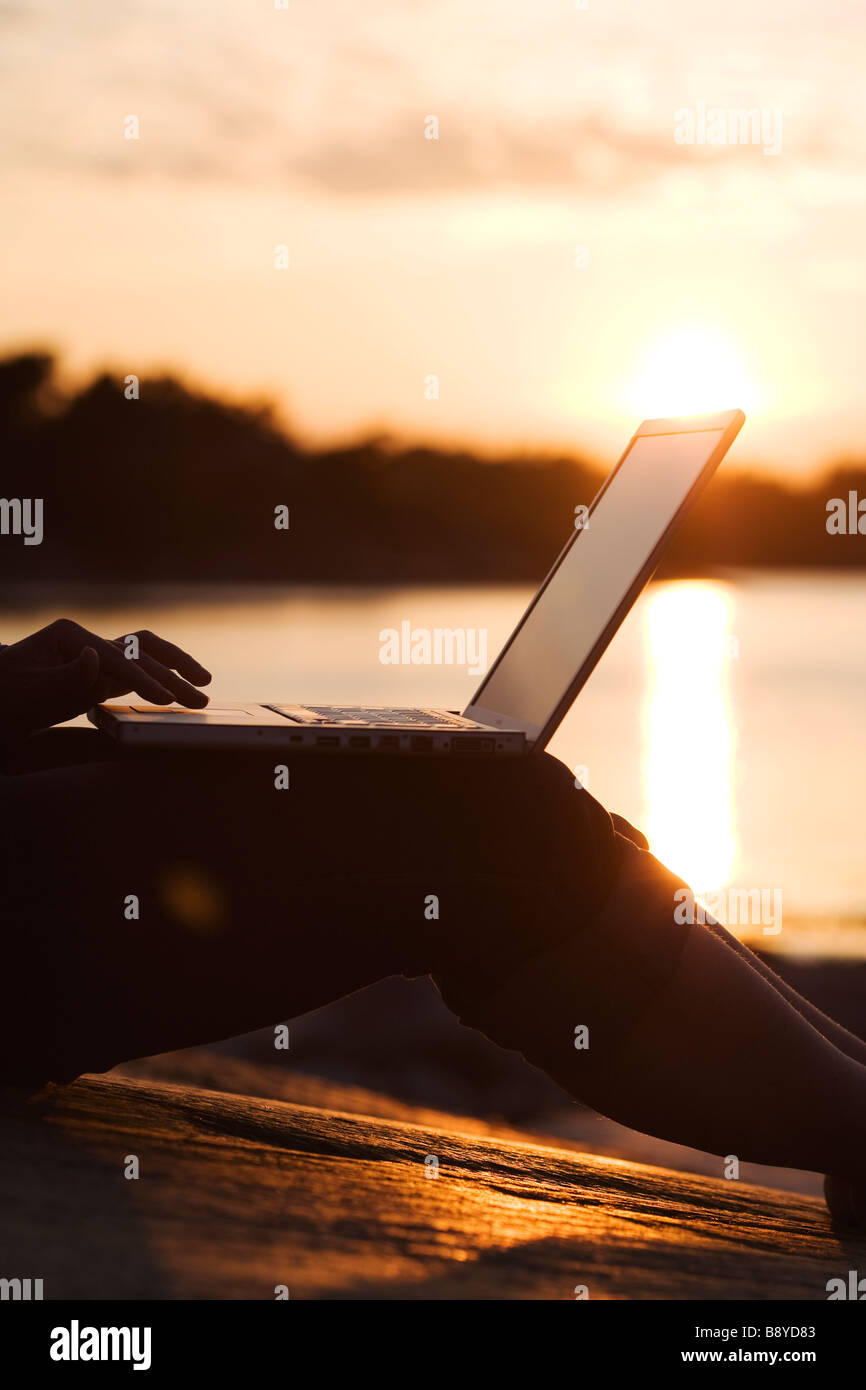 A woman using a laptop Stockholm archipelago Sweden. - Stock Image