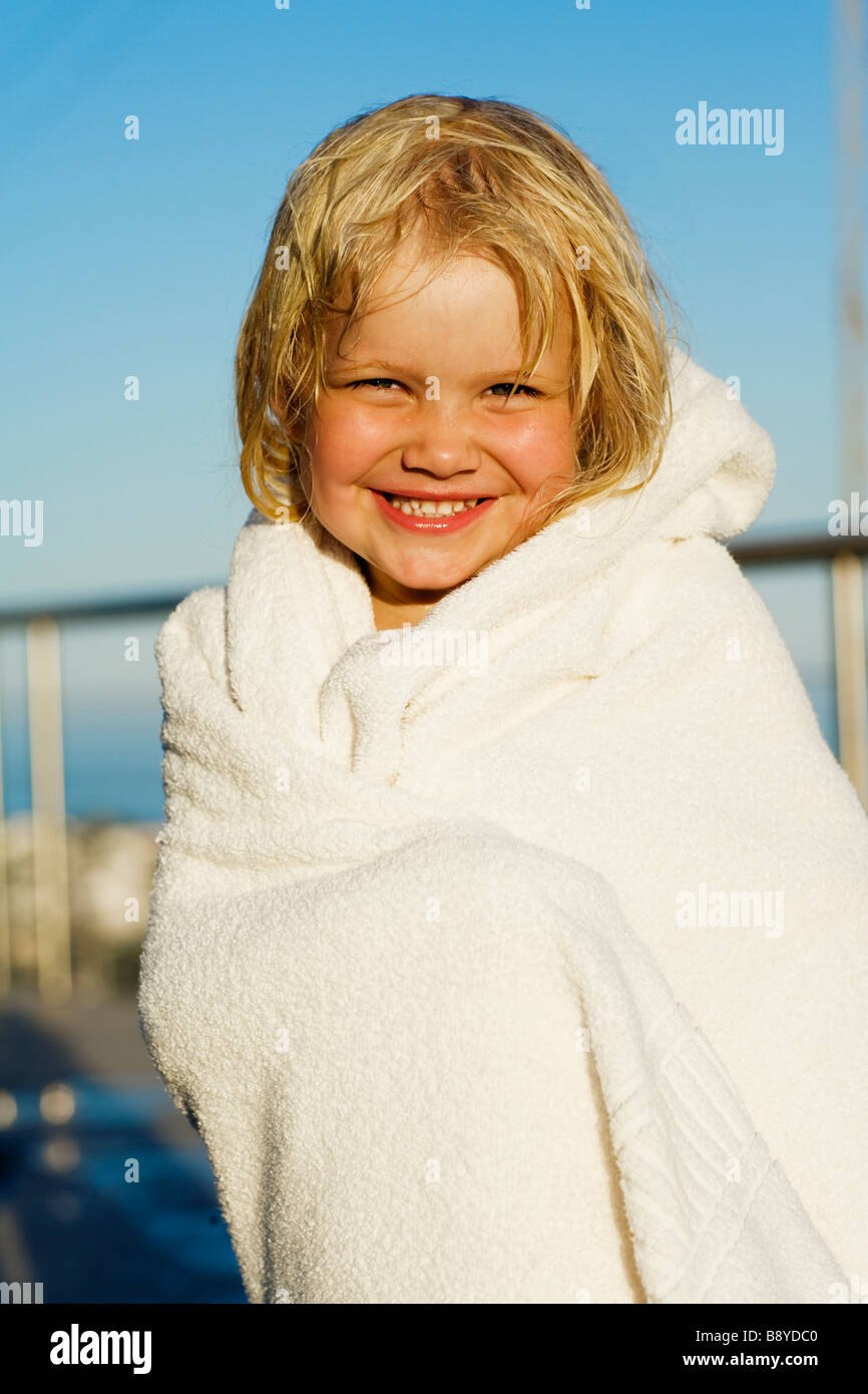 A little Scandinavian girl wrapped in a towel. - Stock Image